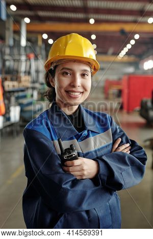 Young successful female worker of modern industrial plant in workwear and protective helmet standing in front of camera in large workshop
