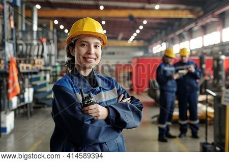 Young smiling female worker of modern industrial plant or factory in workwear and protective helmet standing in large workshop