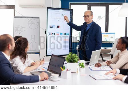Experienced Project Leader Analysing Financial Presentation During Business Conference