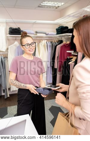 Young saleswoman holding payment terminal while customer paying for her purchases in the clothing store