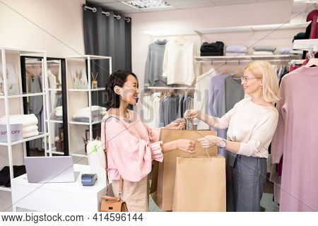 Asian young customer buying clothes in the store while saleswoman giving her shopping bags with smile