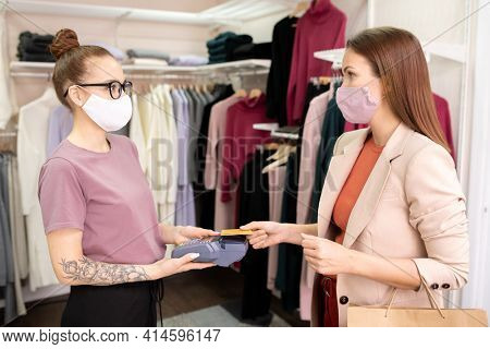 Young woman paying with credit card for her purchases with saleswoman standing opposite her with payment terminal during pandemic in the shop