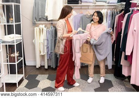 Two young women discussing new clothes together before purchase in clothes shop
