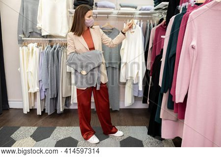 Young pretty saleswoman in protective mask hanging new clothes on the rack while working in clothing shop