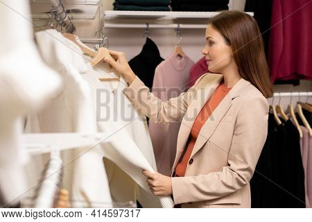 Young woman holding new jumper and choosing it for herself in the clothes shop