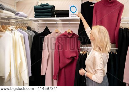 Rear view of saleswoman working in clothing store she standing near the rack with clothes and putting things in order