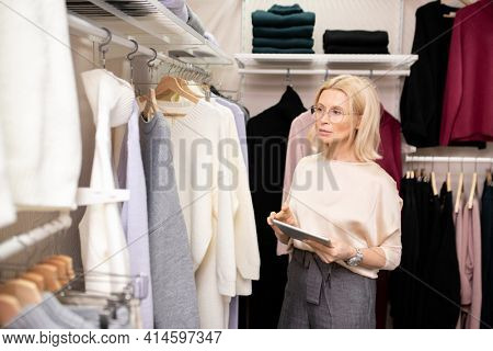 Mature elegant saleswoman using digital tablet while working in clothing store