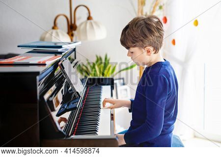 Beautiful Little Kid Boy Playing Piano In Living Room. Child Having Fun With Learning To Play Music