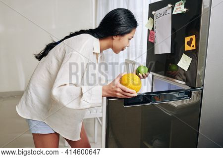 Young Asian Woman In Loungewear Taking Fruits Out Of Refrigerator To Have Some Snacks Or Make Smooth