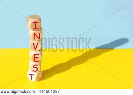 The Word Invest On Wooden Cubes Against Yellow And Blue Background. Financial Investment Growth Or I