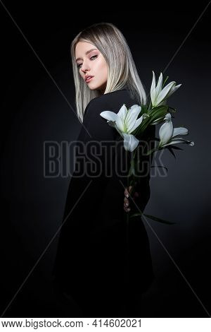 Woman Colored Hair Color Of A Blonde With Lily Flower On Black Background. Coloring Hair Woman Model