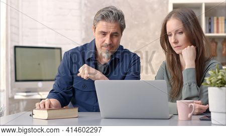 Business people working in office with laptop computer. Happy couple working from home at desk. Talking, meeting, cooperation, entrepreneurs, advisor.