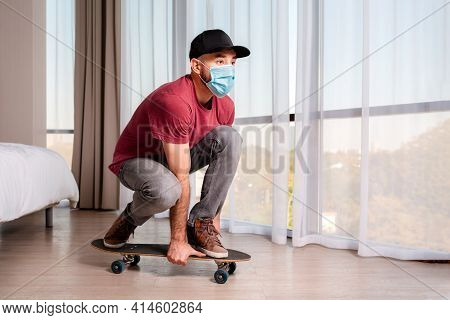 A Young Man In A Medical Mask Poses, Sitting On A Longboard. Indoor. Home. The Concept Of Quarantine