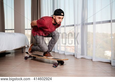 A Young Man On A Longboard, Imagining That He Is Driving Down The Street. Indoor. Concept Of Quarant