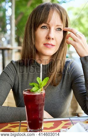 Portrait of attractive happy young woman daydreaming on cafeteria terrace drinking cocktail.
