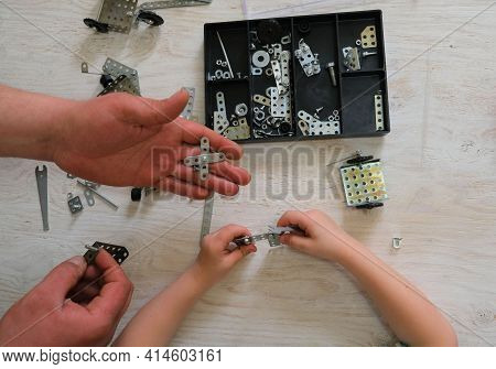 Child And  Dad Assemble A Construction Kit. Screw Driver, Nuts, Wrench, Bolts And Parts Of Children'