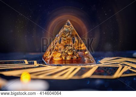 A Glass Pyramid With A Golden Frog With Magic Aura. Tarot Cards Are Scattered On The Table. Close-up