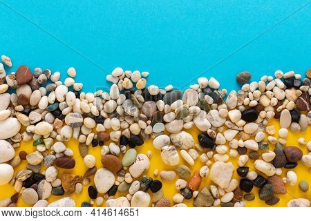 Sea Pebbles On A Blue And Yellow Background