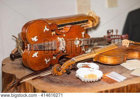 Baroque Wooden Violin On A Tree Trunk Near Other Instruments.