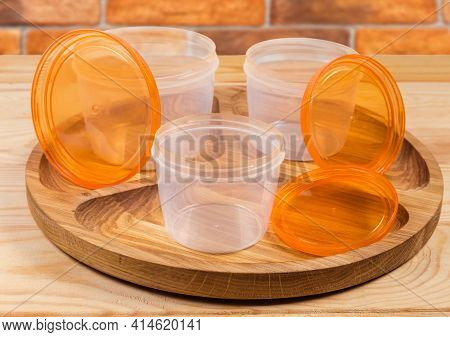 Three Empty Different Sizes Translucent Plastic Food Storage Containers With Open Screw Lids Orange