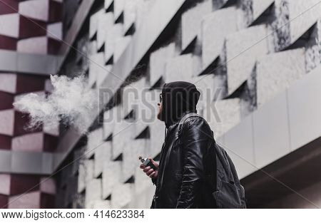 Vape Man. Portrait Of A Handsome Young White Guy In Hood Vaping And Letting Off Puffs Of Steam From