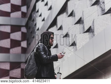 Fashion Bearded Male Dressed In Leather Jacket, Glasses And Hood Vaping. Man In Holding A Mod. A Clo