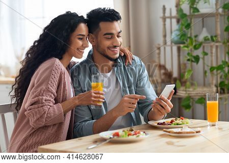 Cheerful Arab Spouses Using Smartphone While Eating Breakfast In Kitchen