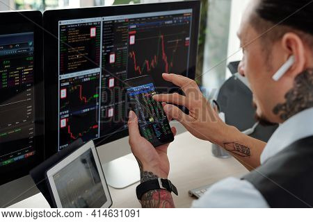 Trader Checking Stock Market Charts On Computer Screens And Buying Stocks Via Application On Smartph