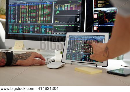 Close-up Image Of Trader Checking Stock Market Data On Screens Of Computer And Tablet Computer