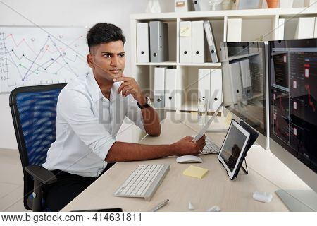 Frowning Pensive Young Indian Trader Monitoring Stock Market Looking At Screens Analyzing Stock Pric