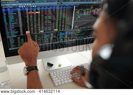Trader Pointing At Computer Screen With Financial Data And Planning What To Buy After Stock Market A