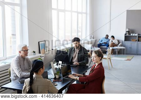 Wide Angle Portrait Of Diverse Group Of Business People Using Computers During Meeting In Modern Off