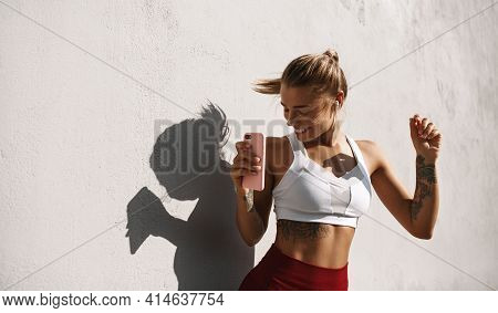 Female Athlete Dancing Outdoors. Sport Woman Dancing With Phone, Listen Music On Run Workout, Runner