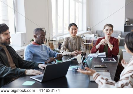 Diverse Group Of Business People At Table During Briefing Meeting In Office, Focus On Smiling Asian
