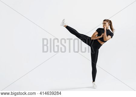 Determined Sport Woman In Activewear Do High Kick, Tae-bo Martial Arts Exercises Isolated On White B
