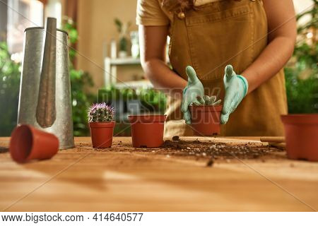 Farmer Girl Transplant Plants Into Pots With Earth.girl In Overalls Standing At The Table And Works.