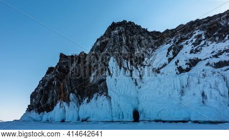 The Steep Slopes Of The Rock Are Covered With Bizarre Ice Splashes And Icicles. At The Base There Is