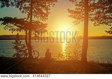 Summer vacation landscape, unidentified tourist girl with bicycle at the edge of the cliff looking the sun setting behind the mountains. Summer vacation concept,summer vacation background,summer vacation sunset