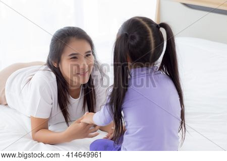 Young Asian Mom And Daughter Smiling And Eye Contact Together With Care In Room, Face Of Mother And