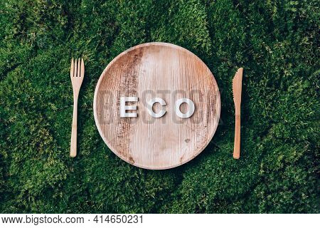 Wooden Disposable Tableware From Natural Materials With Word Eco, Wooden Spoon, Fork On Green Moss B