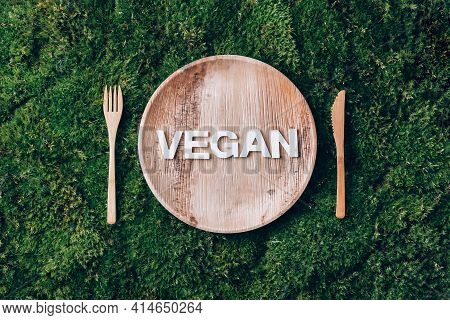 Wooden Disposable Tableware From Natural Materials With Word Vegan, Wooden Spoon, Fork On Green Moss