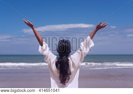 People And Healthy Lifestyle Concept - Back View Young Woman Enjoying Tropical Sea View With Arms Up