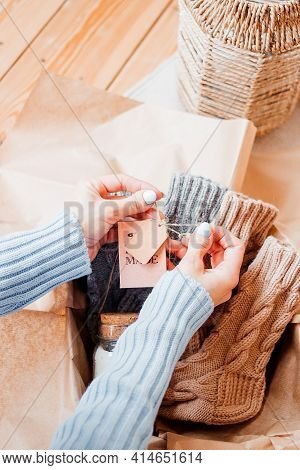Womens Hands Hang A Tag On Knitwear. Needlework