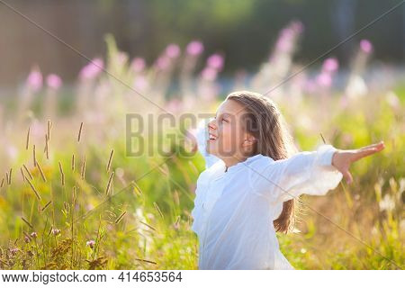 13 Year Old Girl Stands On Blooming Field In Summer Time And Enjoys Clean Air And Freedom. Child Hol