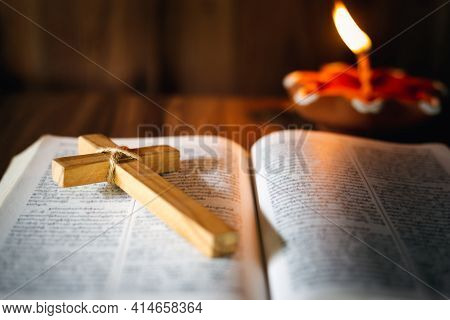 The Cross Is Placed On The Bible. While There Is A Lit Candle. Christian Religious Concept, The Cruc