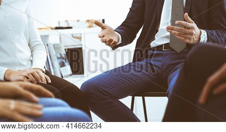 Group Of People Sitting In A Circle During Therapy In Office. Meeting Of Business Team Participating