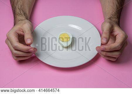 A Boiled Egg Cut In Half On A Plate. Hands At Breakfast. Healthy Breakfast. Boiled Egg On A Pink Bac
