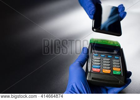 Contactless Payment Operation, Hands In Blue Gloves Holding Contactless Terminal And Smartphone On O
