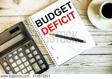 Budget Deficit Written On White Paper Near Coffee And Calculator On A Light Wooden Table. Business C