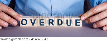 The Word Overdue Is Made Up Of Wooden Cubes By A Man. Business Concept